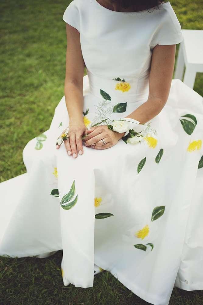 wedding planner Maria Mayer foto di Maria seduta al suo matrimonio primaverile con abito in seta confezionato e dipinto a mano appositamente
